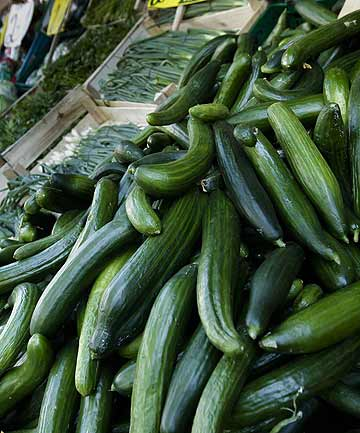 Cucumbers displayed for sale between other vegetables outside a supermarket in Berlin.