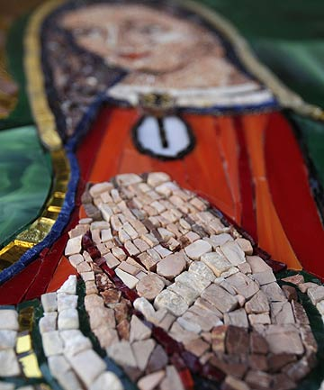 Stones that make up the hands of an image of the Virgin of Guadalupe riding a surfboard are seen in a piece of artwork that hangs under a train bridge in Encinitas.