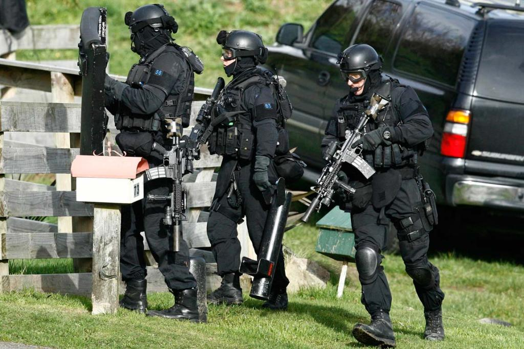 Members of the armed offendeders squad surround a house in Coast Rd.