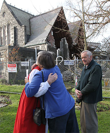 PRAISED PAST: Bishop Victoria Matthews consoles Beryl Dineen at the deconsecrated Holy Trinity Church on Stanmore Road. At right is Dineen's husband, Ray.