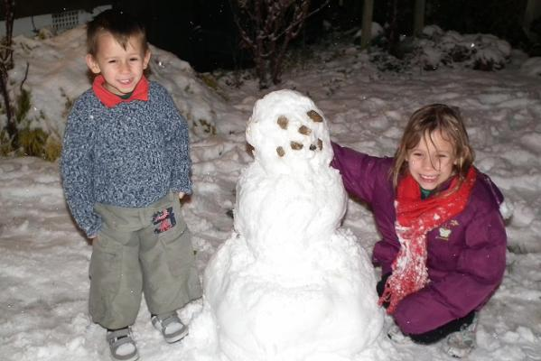 Jaidyn and Kaylah, with their snowman in Opawa.