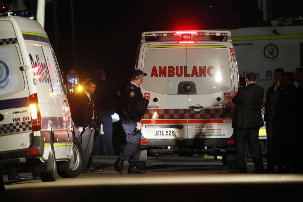 An ambulance arrives outside a house where bomb squad officers eventually freed an 18-year-old Sydney girl who had been trapped for 10 hours with a bomb around her neck.