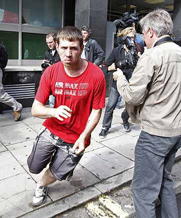 David O'Neill, 22, attempts to avoid the waiting media as he runs from City of Westminster Magistrates' Court after he was released on bail, on charges relating to the London riots.
