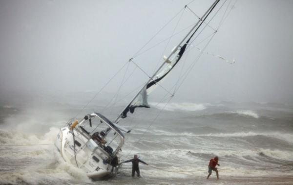 One of two people rescued from a sailboat (right) uses a line to make their way onto the beach on Willoughby Spit in Norfolk, Virginia after they, and another person, were rescued from the boat that foundered in the waters of the Chesapeake Bay.