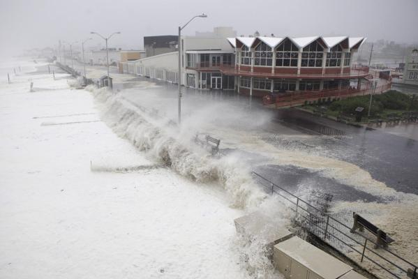 Waves pound the boardwalk and the beach at first light as Hurricane Irene slams into Asbury Park, New Jersey.