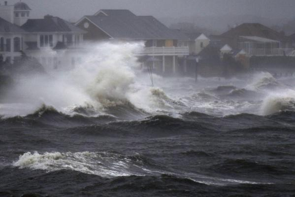 Waves crash over the shore during high tide during a storm surge from Hurricane Irene in Bayshore, New York, on Long Island.