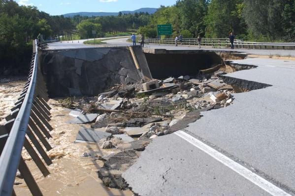 People take photos of a washed-out section of Route 7 south of Rutland, Vermont, following heavy rains from Tropical Storm Irene that swelled rivers the day before.