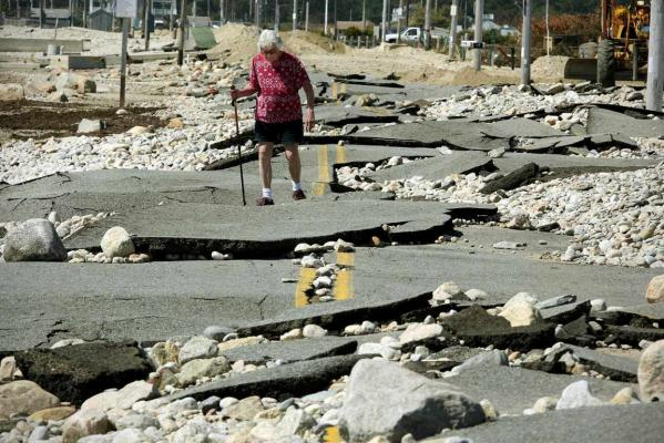 Pat Richard tries to make her way along what remains of East Beach Road in Westport, Massachusetts that was shattered by high surf and winds when Tropical Storm Irene swept the area.