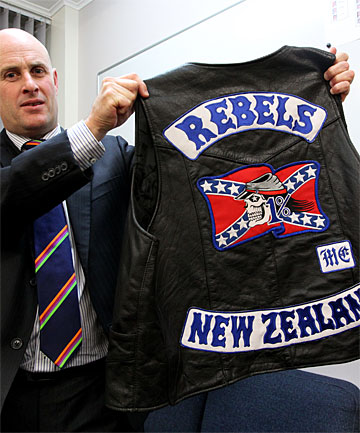 ORGANISED EFFORT: Detective Inspector Chris Bensemann displays a Rebels gang patch after yesterday's raid.
