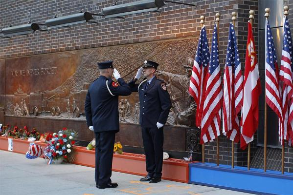 New York City firefighters salute each other outside Ladder Company 10 at the south border of the World Trade Center site on the 10th anniversary of the 9/11 attacks.