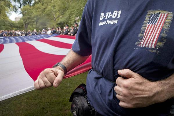 A man holds a large American flag during a ceremony honoring firefighters and public servants killed in the 9/11 attacks on the World Trade Center, on the 10th anniversary, in New York.
