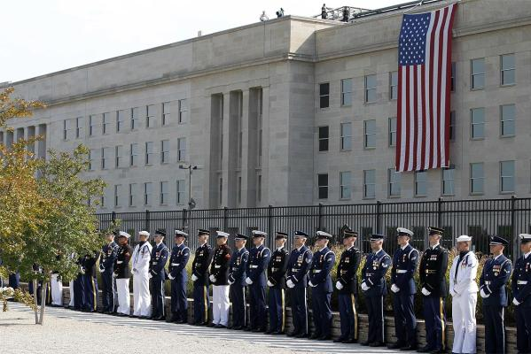 Members of the different services of the US military stand at attention as a United States flag hangs over the side of the Pentagon hit by a hijacked airliner durng the 9/11 terror attacks.