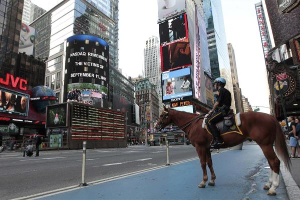 A mounted police officer watches ceremonies marking the 10th anniversary of the 9/11 attacks on the World Trade Center on a screen in New York's Times Square.