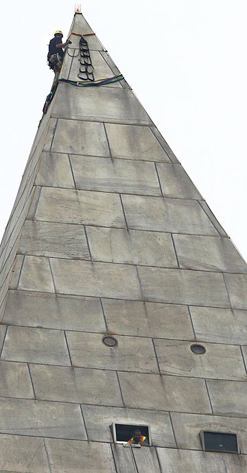 A man attaches rigging to the top of the Washington Monument before engineers rappeled down the sides of the monument to survey the extent of damage sustained from the August 23 quake.