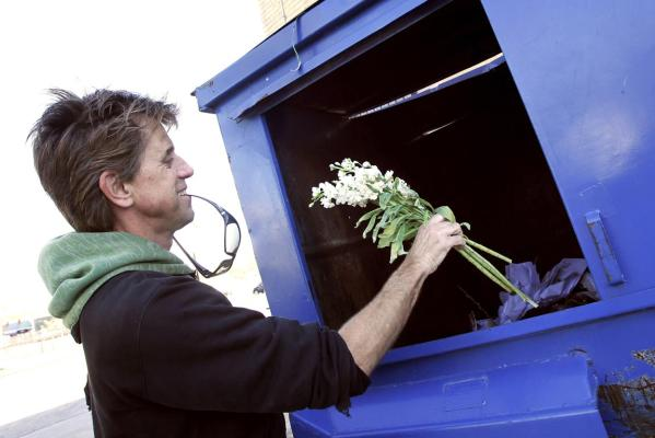Jeff Ferrell, a professor of sociology at Texas Christian University, pulls discarded flowers out of a dumpster behind a florist shop in Fort Worth, Texas.