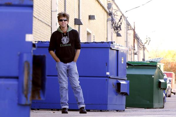 Jeff Ferrell, a professor of sociology at Texas Christian University, is pictured next to a trash dumpster in Fort Worth, Tex