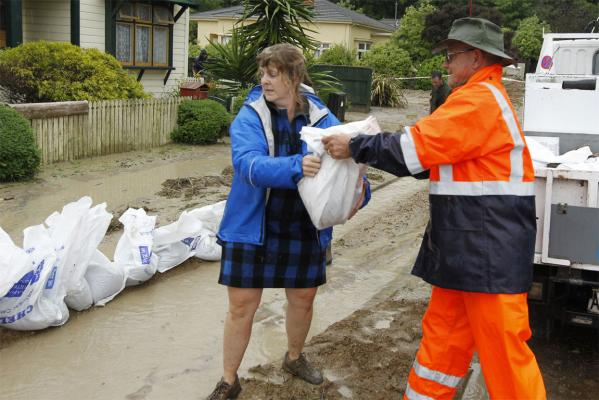 Jennie Warr of Grove Street helps Dean Merry of Nelson City Council to place sandbags along the street.