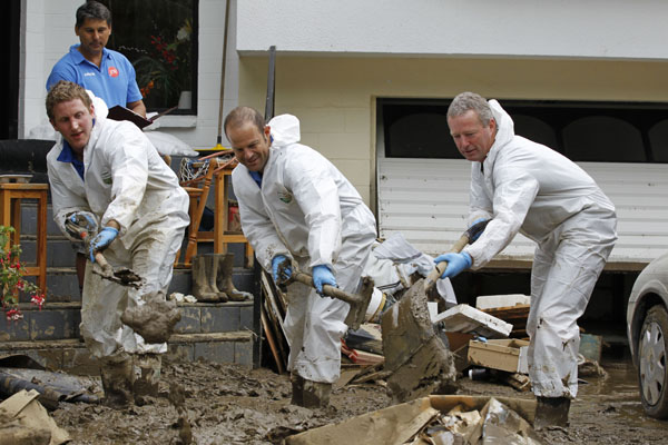 Dressed for the occasion. Tim Vincent of Hamilton, left, Neil Dawkins of Nelson, centre, and Wayne Nelson of Kaikoura, right, work together with Arron Flavell of Jae's Kaikoura, background, in an organised clean-up operation at flood damaged 219 Nile Street.