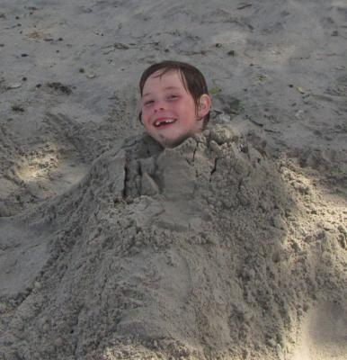 BURIED ALIVE: Noleen Sommerville has some fun in the sand and hopes the tide stays out.