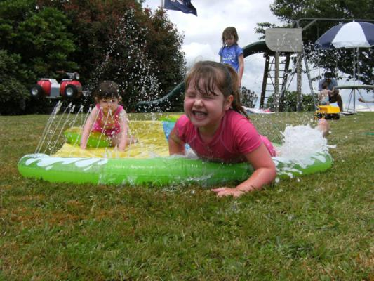 SLIPPY SIDE: From left, Breanna Goodwin, 3, Zoe Heayns, 4, and Kiera Heayns, 6, have some fun at their grandparent's house at Owhango on Christmas Day.