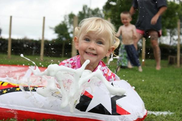 SPLISH SPLASH: Regan Trubshaw, 3, of Cambridge makes the most of some decent weather and a soapy waterslide in the back yard.