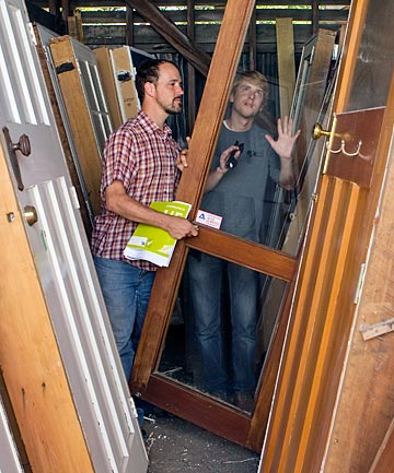 Tim Bishop, left, of SHAC, and Clayton Prest, of Gapfiller, select a door from Pumphouse Demolition for an office made from recycled materials.
