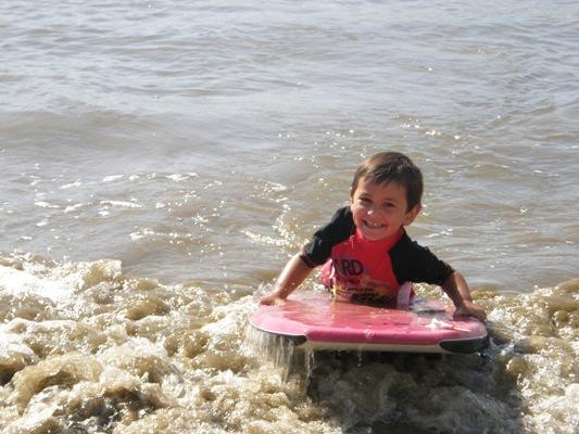 Surf's up: Keri Wynyard pictured Cooper, 4, hitting the waves in Oakura Bay in Northland.