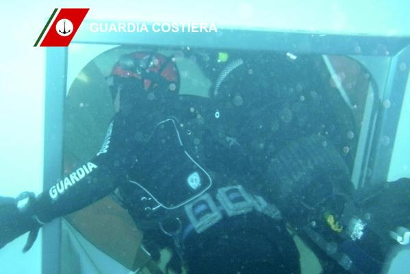 An Italian Coast guard diver inspects the Costa Concordia cruise ship that ran aground off the