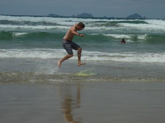 IN MOTION: A keen beach-goer is captured mid-air as he prepares to skim across the water.