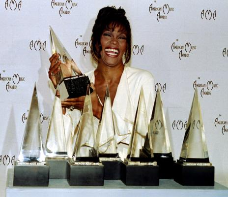 Whitney Houston shows off the seven awards she won at the 21st American Music Awards in 1994.