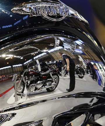 Motorcycles are reflected in the fuel tank of a Triumph Rocket during the International Motorcycle and Scooter show in Birmingham, central England.