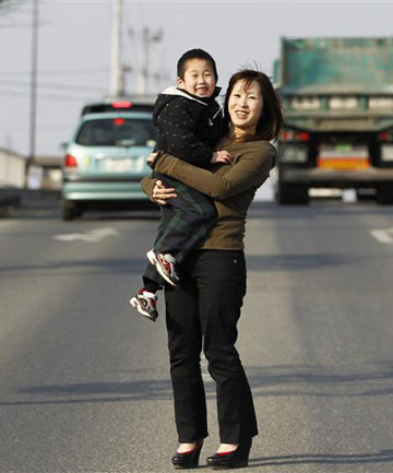 Yuko Sugimoto and her son, Raito, at the same place she stood in March 13, 2011 after the area was hit by an earthquake and tsunami in Ishinomaki, Miyagi prefecture in northern Japan.