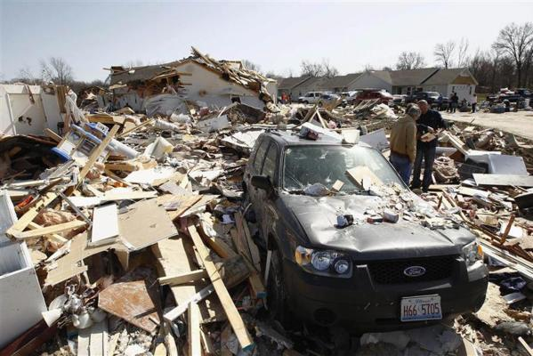 People search for photos and other personal belongings among the rubble caused by a tornado in Harrisburg, Illinois.