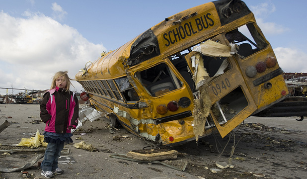 WEATHER BEATEN: Student Madeline Evans walks past a destroyed school bus after a tornado devastated the town of Henryville, Indiana.