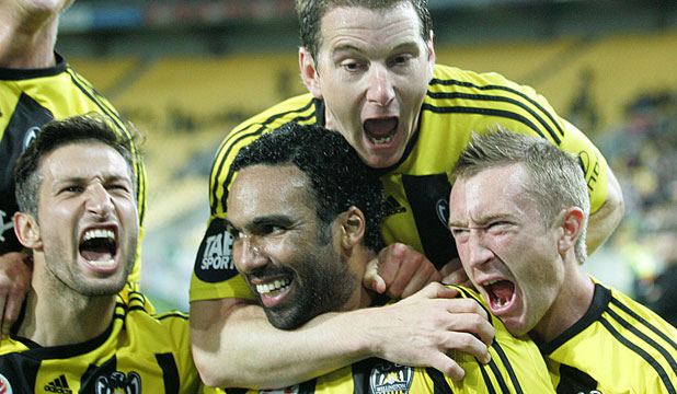 Paul Ifill is swamped by teammates after scoring from the penalty spot.