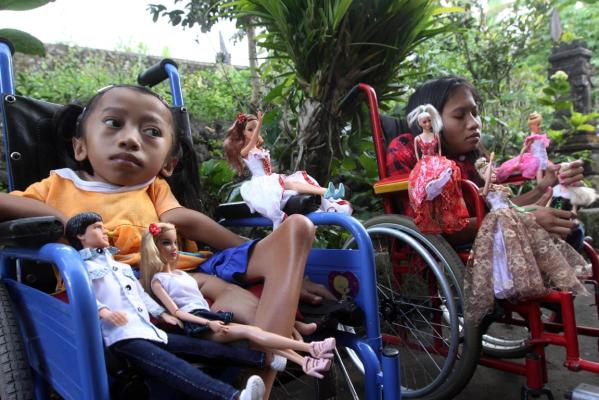 Sisters Alit Astini (right) and Putu Restiti display Barbie dolls as they sit in wheel chairs outside their house in Songan village, Kintamani, Bali, Indonesia.