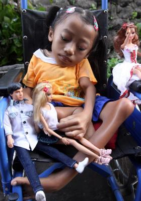 Alit Astini displays Barbie dolls as she sits in a wheel chair outside her house in Songan village, Kintamani, Bali, Indonesia.