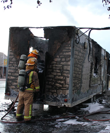 Alexandra Fire Brigade firefighters hose hot spots after a large fire gutted the Alexandra Pie Cart on Saturday aft