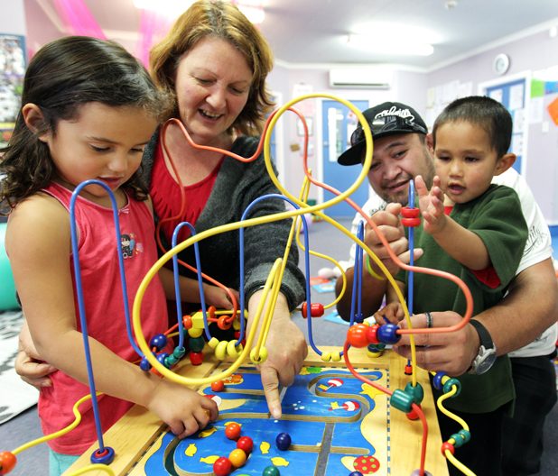 LEARNING TIME: Sienna Moore and Timothy Carter, both 3,   play with tumaki Tere Gilbert and  Des Tipene a Pouwhakahaere  at Te Kohanga Reo O Nga Kuaka.