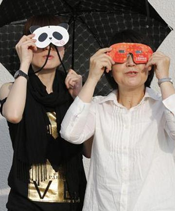 Women watch a partial eclipse in Tokyo as the sun and moon align over Earth in a rare astronomical event .