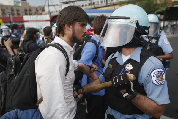 A protester clashes with a police officer in riot gear during an anti-Nato protest march in Chicago.