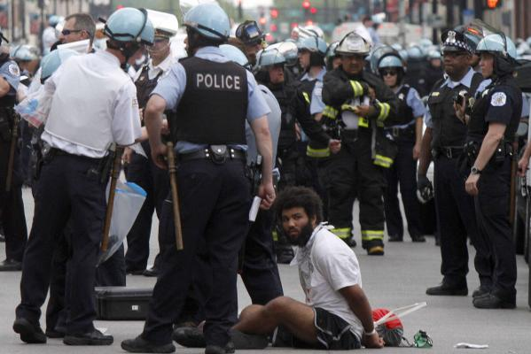 A protester sits handcuffed after being arrested during a march where Chicago Police use batons in an attempt to clear out over 10,000 protestors marching through downtown Chicago during an anti-Nato protest march.