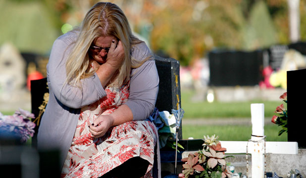 Grieving mother Trish Samson sits at her son Jacob's grave.