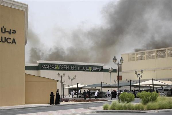 Firefighters attempt to extinguish a fire at the Villaggio Mall in Doha's west end.