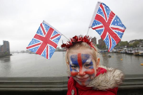 A young spectator waits for the start of the pageant along the River Thames in London.
