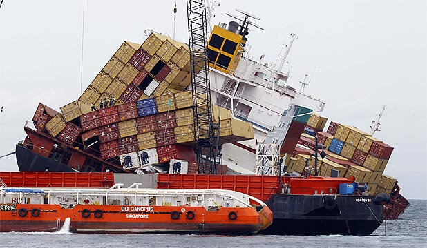 OFFLOADING: Experts continued the painstaking process removing containers from the top le