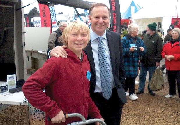 ALL SMILES: Matamata teenager Jacob Lawrence shows his ''grass blaster'' invention to Prime Minister John Key at the National Agricultural Fieldays.