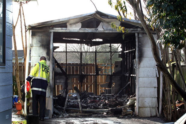 Waikato fire safety officer Kevin Holmes inspects the remains of an Aileen Pl, Nawton, garage this morning after it was torched in a suspicious blaze.