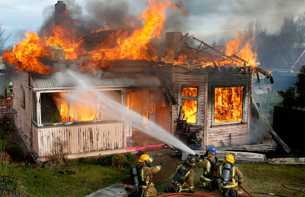The roof collapses as fire consumes the wooden bungalow.