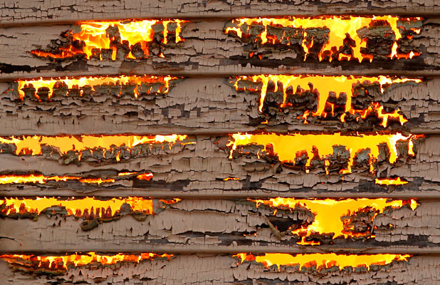 Flames burn through the wooden weather boards of the bungalow.
